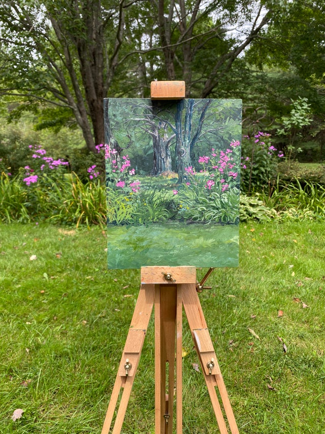 artist's easel holding painting of purple flowers in garden.