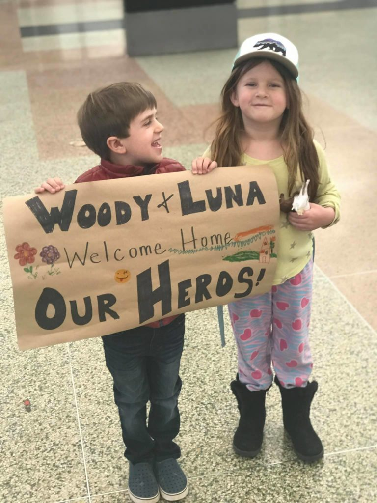 child holding sign that says Woody and Luna our heroes