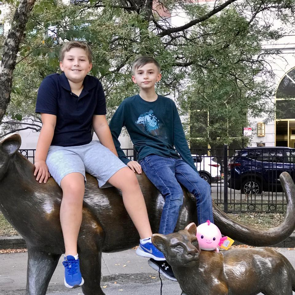 two 11 year old boys sitting next to each other on a statue of a wild cat next to a smaller wild cat stature with a pink stuffed animal on it