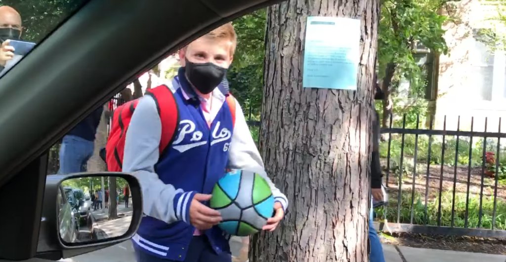 11 year old boy wearing a mask and holding a basketball approaching a car window