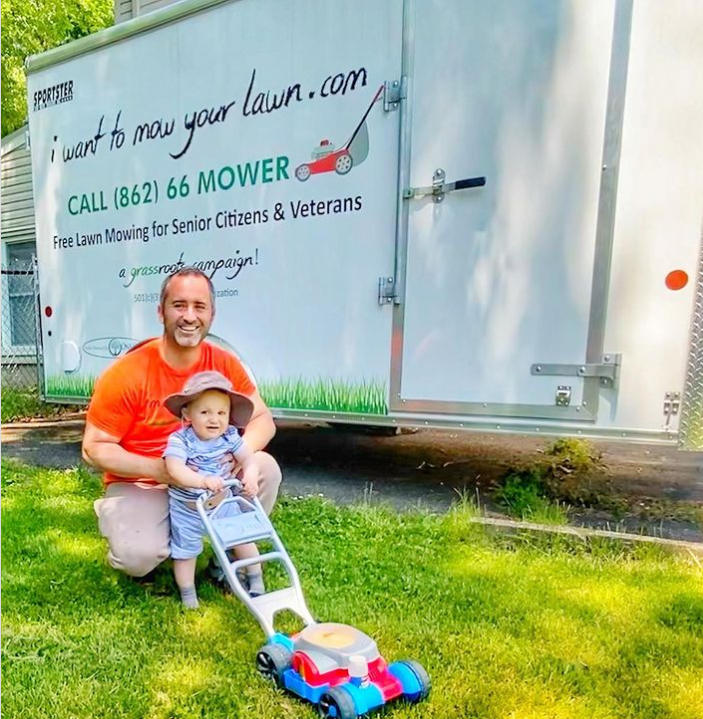 white trailer from i want to mow your lawn with a man squatting down and holding a baby who is holding the handle of a toy lawn mower