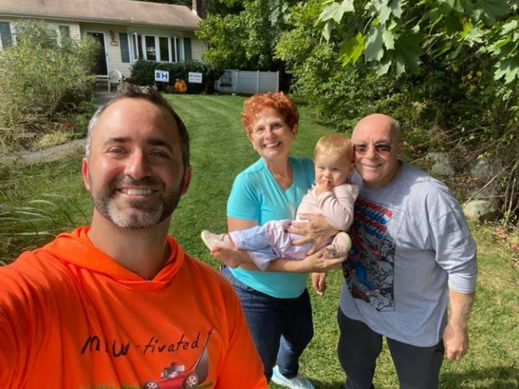 smiling man taking a selfie with a man and a woman who is holding a toddler in a front yard