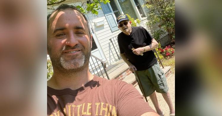 smiling man taking selfie with an older man wearing a korean veteran hat