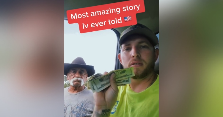 man sitting in a truck and holding money up with a man with a mustache standing next to him