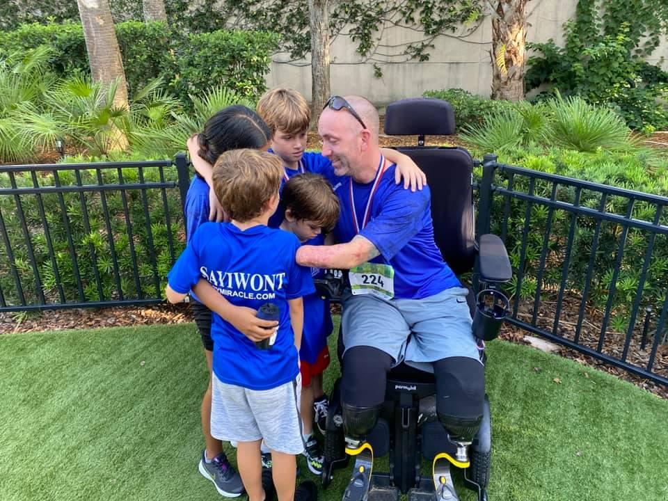 Gary Miracle hugs his kids