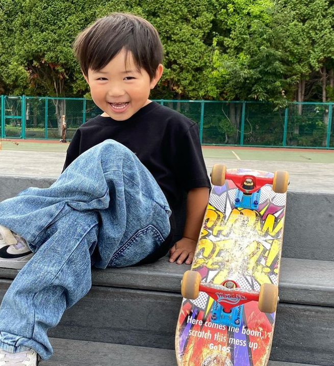 4 year old smiling and sitting on a step outside with his legs crossed next to an upside down skatebaord