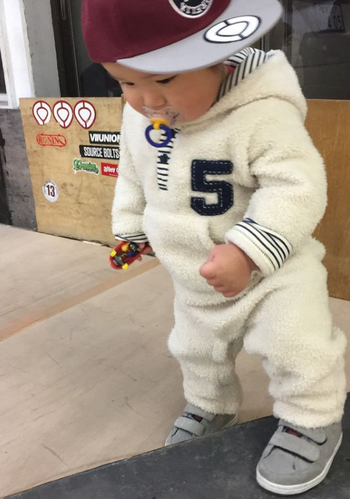toddler wearing a hat and sucking on a pacifier while holding a miniature toy skateboard while standing with one foot on a real skateboard
