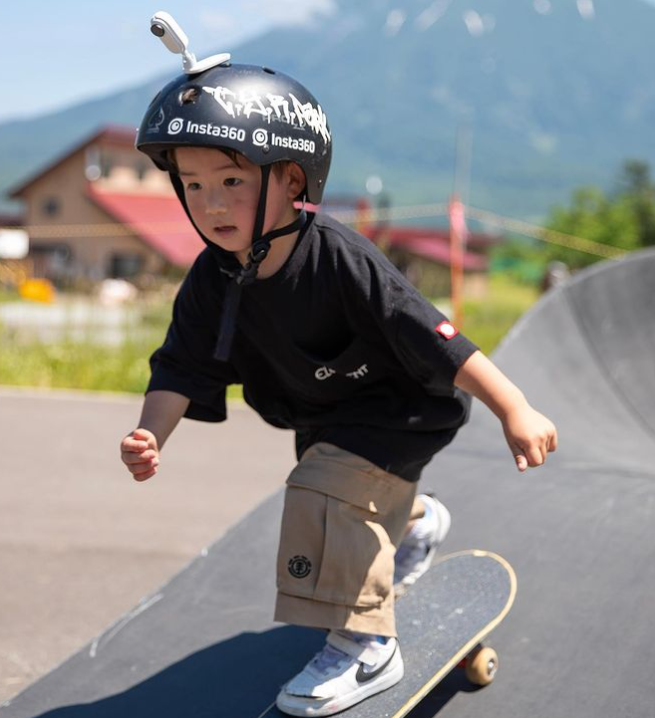 4 year old concentrating as he rides a skateboard while wearing a helmet with a camera attached