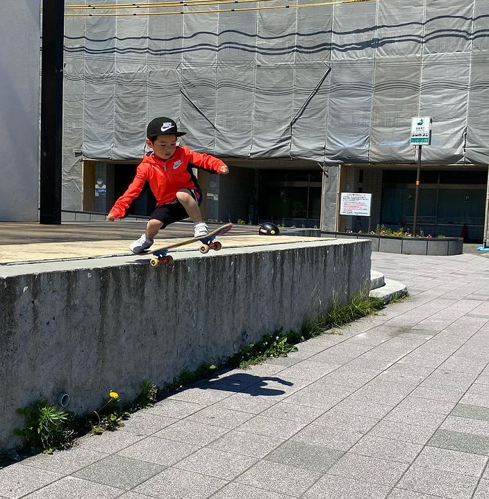 4 year old boy skateboarding off a stage outside
