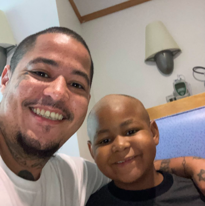 dad and son with shaved heads smiling