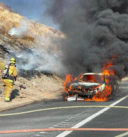 firefighters near burning car