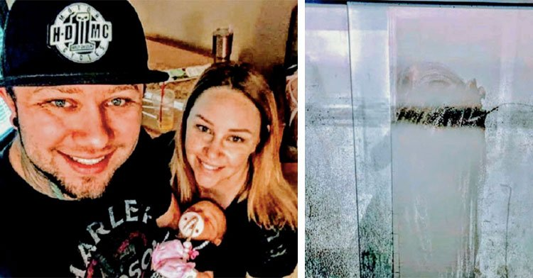 parents holding baby next to wiped off shower pane