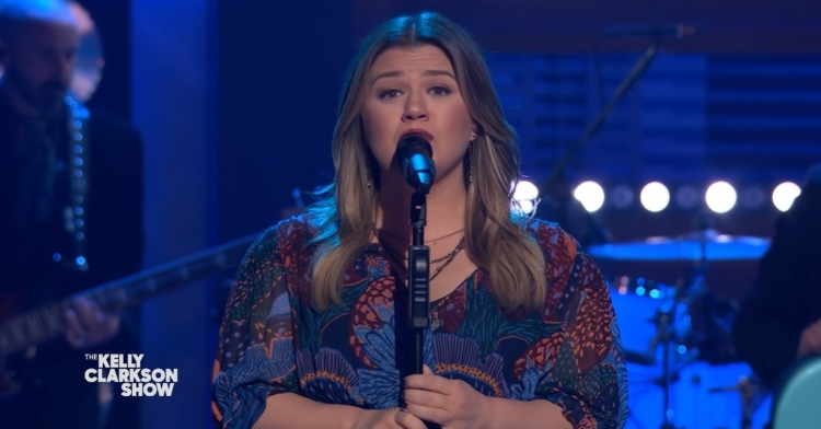 kelly clarkson singing into a microphone on a stand with the kelly clarkson logo at the bottom left corner